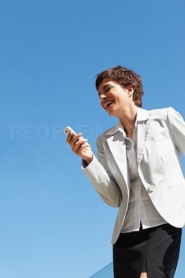 A business woman laughing over a message on her mobile