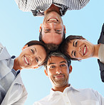 Upward view of a group of happy business colleagues with their heads together