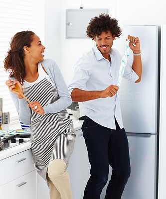 Cute young couple in a playful mood preparing food together