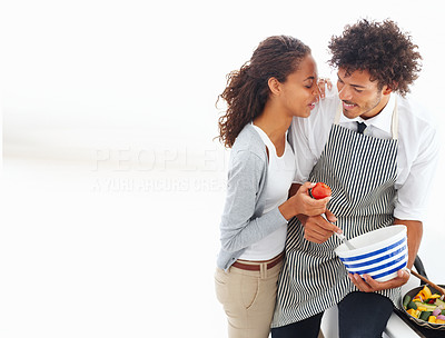 Happy young couple preparing food together over white background
