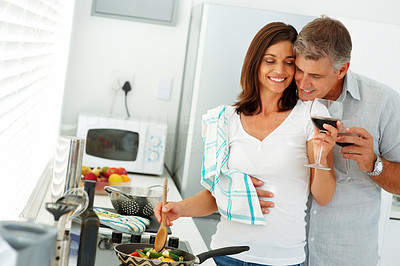 Cute mature couple preparing food together at home