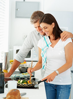 Happy mature couple preparing food together at home