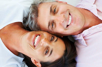 Closeup of a happy mature couple lying down with their heads together