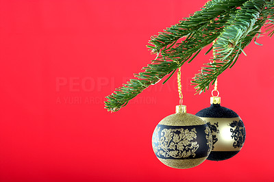 Buy stock photo Cropped detail image of christmas decorations hanging from the branch of a tree, isolated on red - copyspace