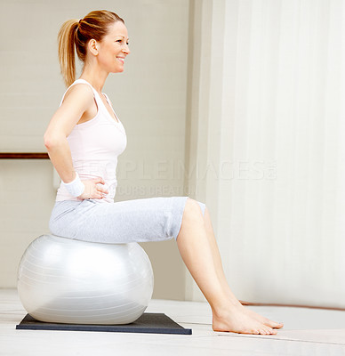 Portrait of fit mature female exercising on a fitness ball