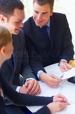 Buy stock photo Cropped shot of a group of corporate businesspeople talking together over paperwork