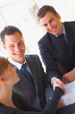 Buy stock photo Shot of a group of corporate businesspeople shaking hands while sitting at a table