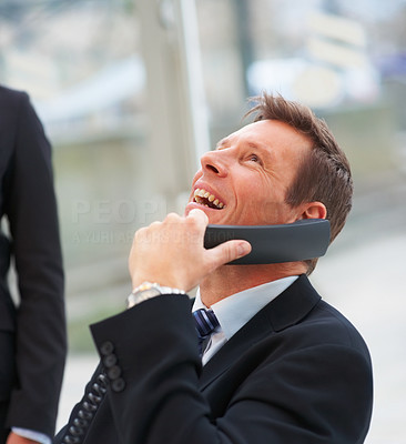 Portrait of happy business man laughing on a conversation on the phone