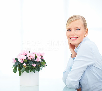 Portrait of smiling female with flower vase on the table
