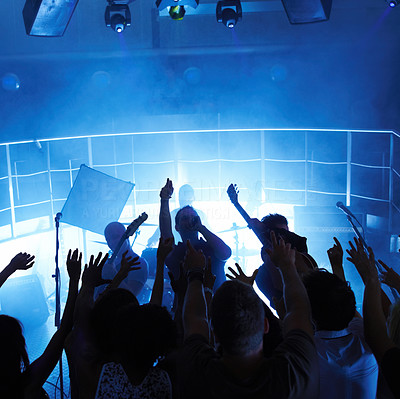 People cheering a rock show in a disco