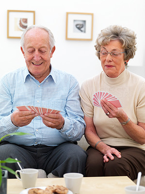 Portrait of a elderly couple playing a game of cards