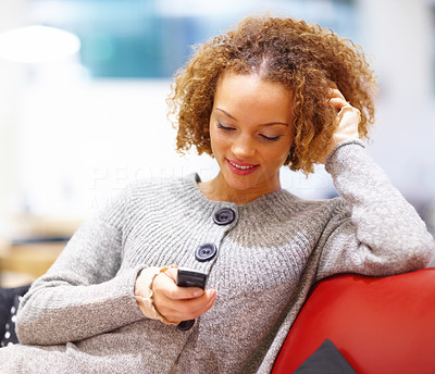 Smiling woman sitting on sofa and text messaging
