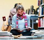 Young lady sitting and reading book in library