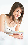 Happy young lady using a laptop and eating fruit salad