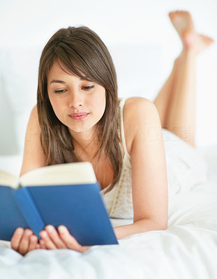 Buy stock photo Beautiful young woman reading a novel in bed