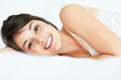Buy stock photo Happy young woman relaxing on the bed