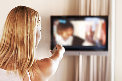Young female at home swapping TV channels