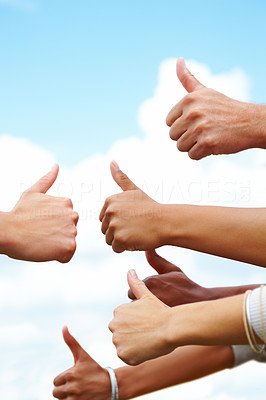 Mixed hands giving thumbs up against the sky
