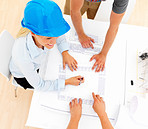Top view of female architect with colleagues working on blue prints
