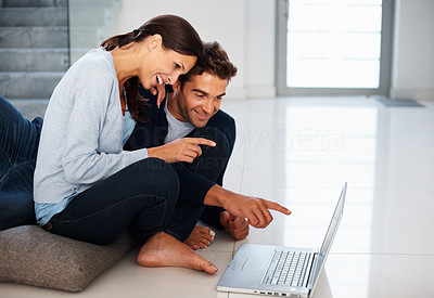 Buy stock photo Attractive couple smiling while pointing at laptop