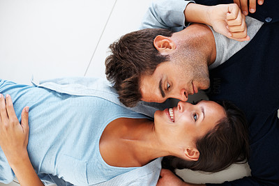 Buy stock photo Attractive couple lying on floor with eyes locked