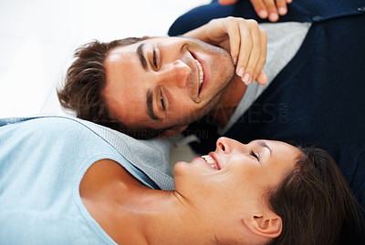 Buy stock photo Attractive couple lying on floor smiling