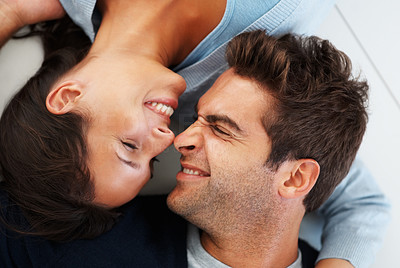 Buy stock photo Playful couple lying on floor making faces