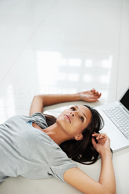 Buy stock photo Pretty woman lying on the floor near laptop