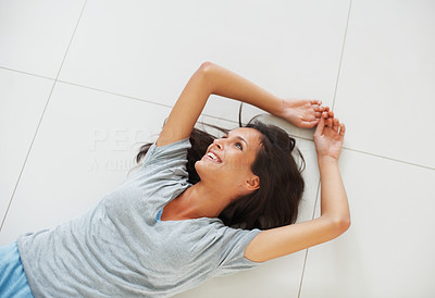 Buy stock photo Pretty woman lying on the floor smiling while looking away