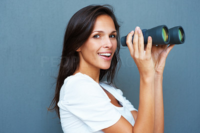 Buy stock photo Side view of pretty woman holding binoculars in front of her against blue background