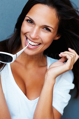 Buy stock photo Pretty woman holding sunglasses between teeth against blue background