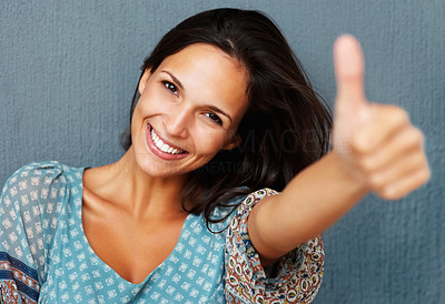 Buy stock photo Woman gives thumb up against blue background