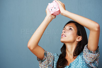 Buy stock photo Brunette holding a piggy bank above her head head
