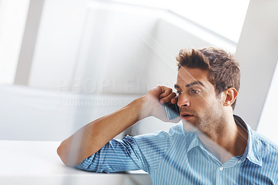 Buy stock photo Shot of an angry young man talking on a mobile phone behind the glass