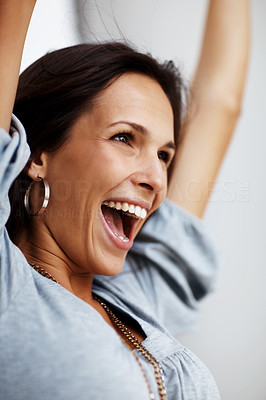 Buy stock photo Closeup portrait of an excited young woman laughing with her hands raised