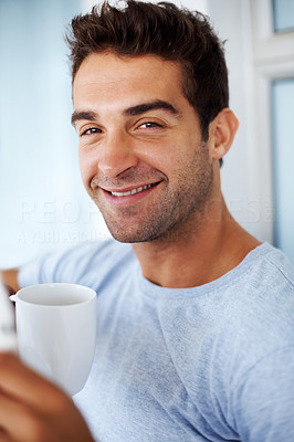 Buy stock photo Portrait of a happy young man enjoying a cup of coffee at home