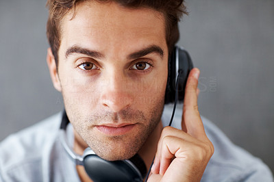 Buy stock photo Closeup portrait of a handsome young man listening to music on headphone against grunge background