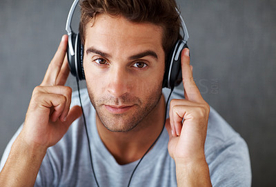Buy stock photo Portrait of a serious young man listening to music on headphones against grunge background