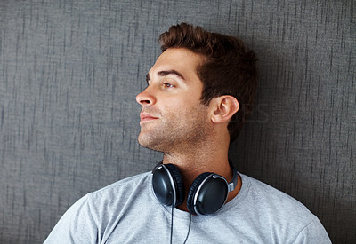 Buy stock photo Portrait of a thoughtful young guy looking away at copyspace against grunge background
