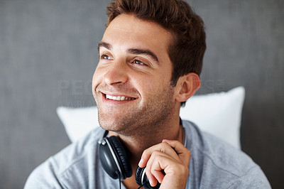 Buy stock photo Shot of a happy young guy looking away and thinking against grunge background