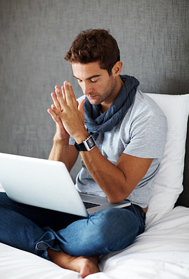 Buy stock photo Portrait of a young man thinking while working on laptop at home