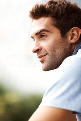 Buy stock photo Shot of a handsome young man looking away in thought