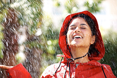 Buy stock photo Young woman wearing a red raincoat enjoying the rain and having fun outside