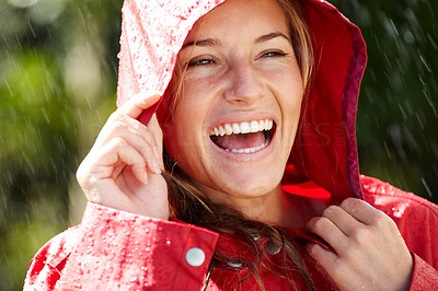 Buy stock photo Closeup of an excited young female holding a red raincoat hat on head - Outdoors