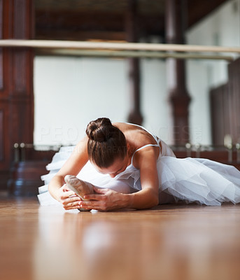 Buy stock photo Portrait of a young ballet dancer stretching on a dance floor in the studio