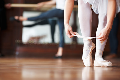 Buy stock photo Closeup portrait of a ballerina puts on Pointe with a blurred man practicing in background