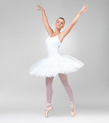 Buy stock photo Full length of a young ballerina wearing white tutu dancing against white background
