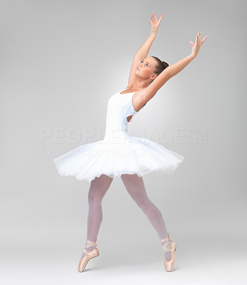 Buy stock photo Full length of a young and beautiful ballerina dancing against white background - copyspace