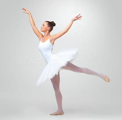 Buy stock photo Full length of a young ballerina dancing gracefully against white background