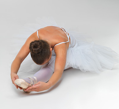 Buy stock photo Portrait of a young ballet dancer stretching against white background